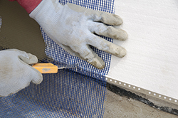 Close up of worker hands cut mesh on styrofoam insulation
